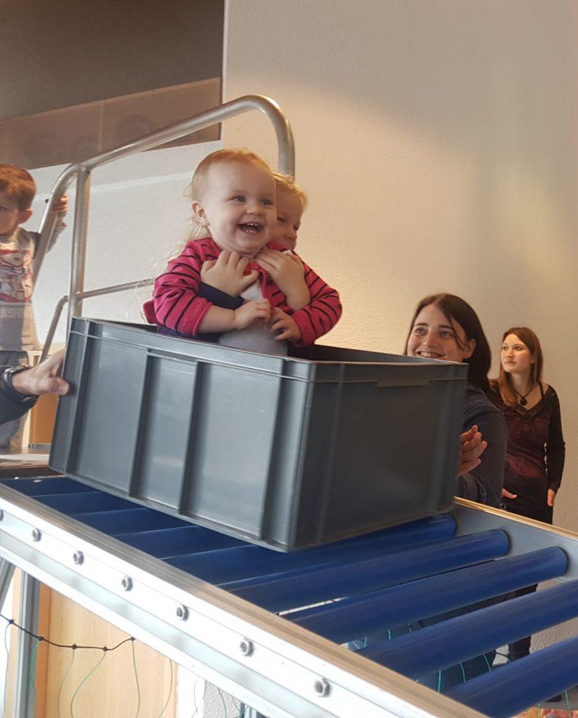 Kinder auf der Rollenrutsche und zwei junge Frauen daneben.