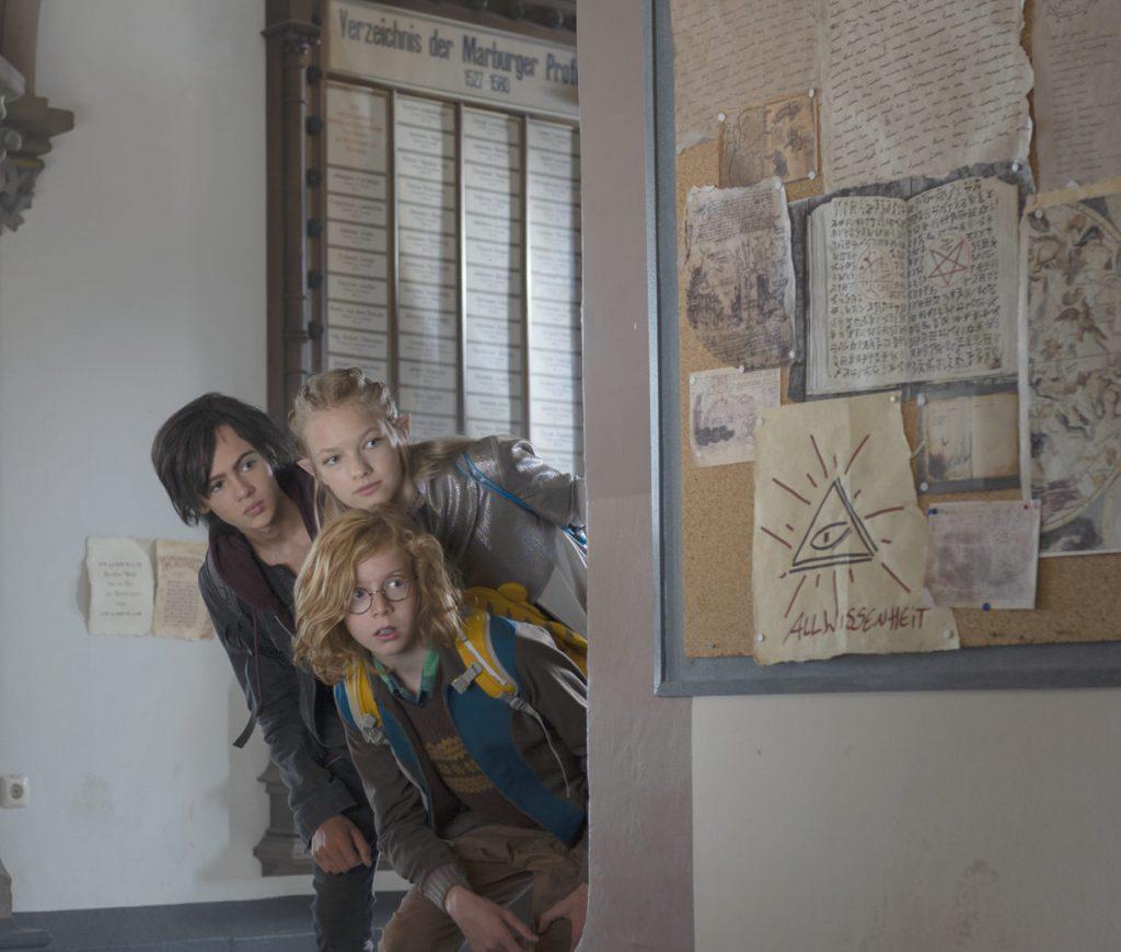 Drei Kinder stehen im Durchgang in der Alten Marburger Universität. Zwei Jungs, dunkelhaarig und rotblond und ein Mädchen mit ungewöhnlich spitzen Ohren und einer blonden Flechtfrisur.