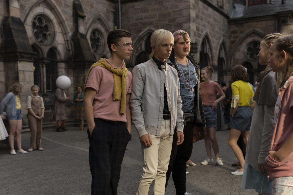 Vor einem historischen Gebäude mit gotisch anmutenden Torbögen stehen drei Jugendliche zwei Teeny-Mächen gegenüber.