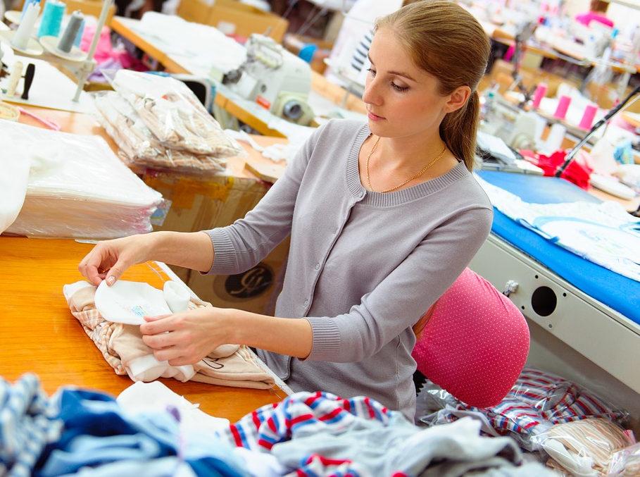 Junge Frau mit Stoffen sitzt am Tisch und legt Teile zum Zuschneiden aufeinander.