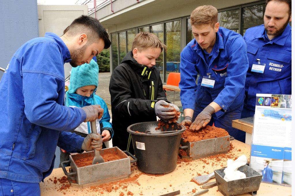 Kinder füllen eine Form mit Spezialsand an einem Ausbildungsstand