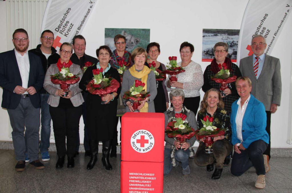 Geehrte mit Blumen und Vorstand des DRK-Kreisverbands stellen sich zum Gruppenfoto.