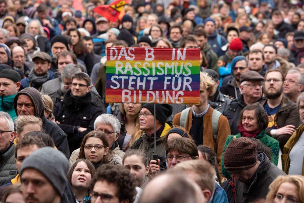 """In der Menge der Demonstranten hält einer ein Schild hoch. """"Das B in Rassismus steht für Bildung""""."""