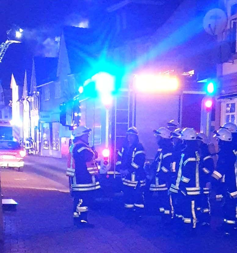 Feuerwehrauto, Einsatzkräfte in Montur. Häuser dahinter.