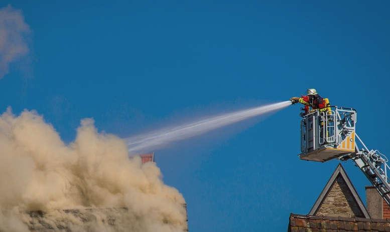 Feuerwehrmann auf Drehleiter löscht brennendes Haus. Enorme Rauchentwicklung