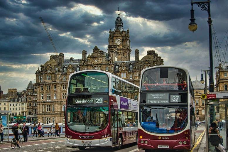 2 moderne Reisebusse vor der Kulisse von Edinburgh .