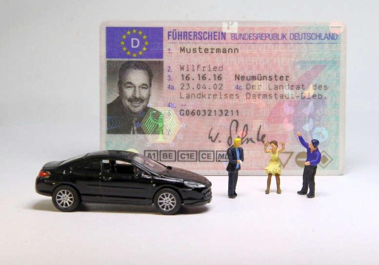"""Ein Führerschein. Davor ein Matchbox-Auto und drei Mini-Figuren die sich """"streiten""""."""