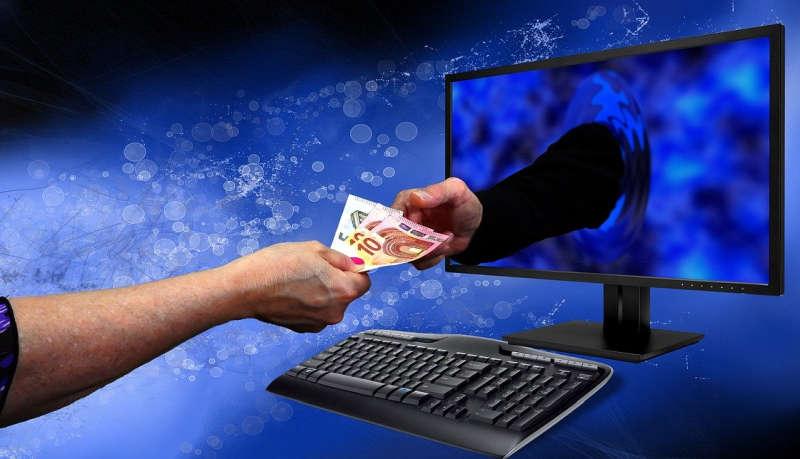 Ein Mensch reicht Geld an einen Arm der aus dem PC-Monitor herausragt.