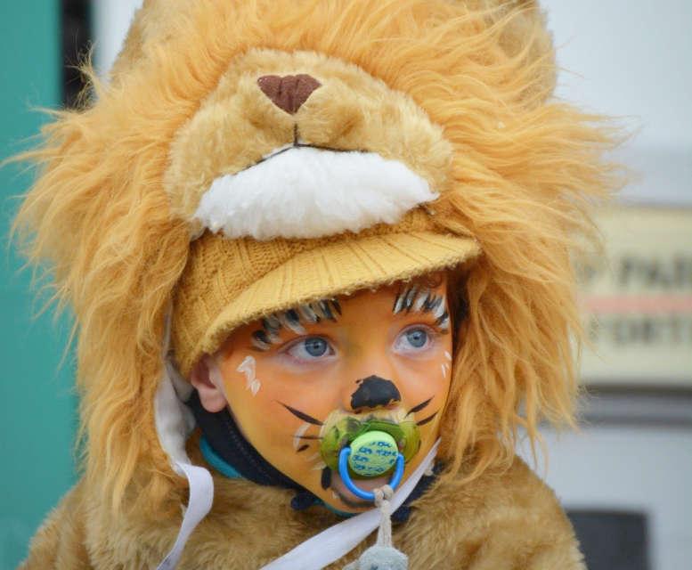 Kind als Löwe verkleidet und bemalt. Mit Schnuller im Mund.