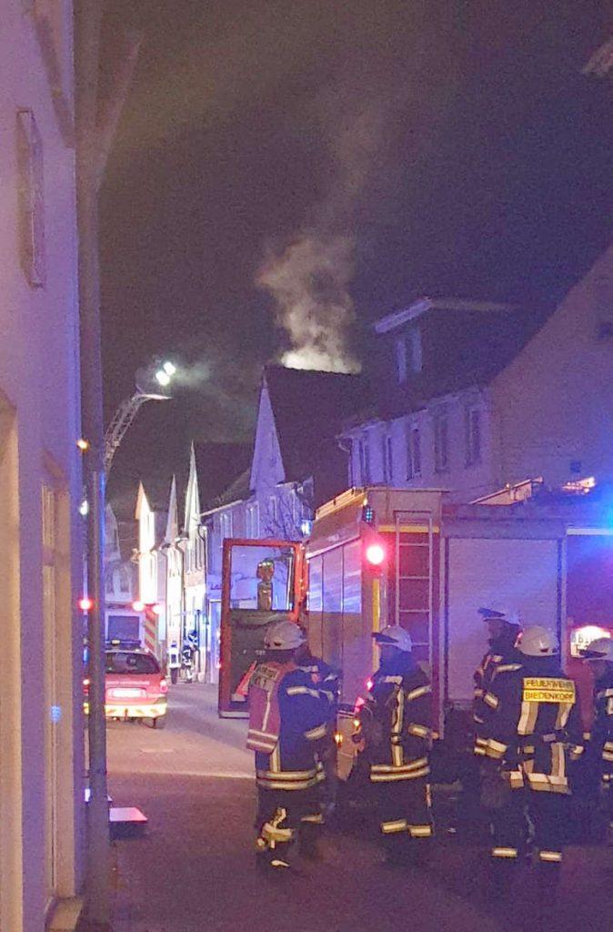 Feuerwehrleute steigen aus dem Einsatzfahrzeug. Hinter einem der Häuser am Straßenrand steigt Rauch auf.