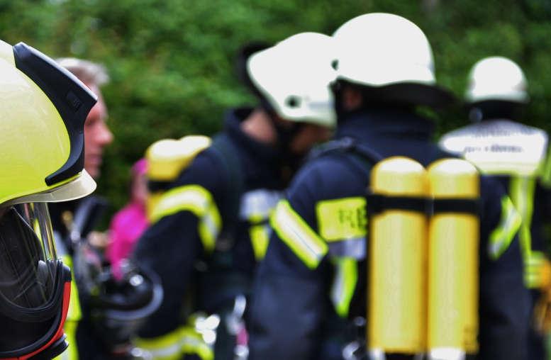 Feuerwehrleute mit Atemschutz stehen herum und warten auf den Einsatz.