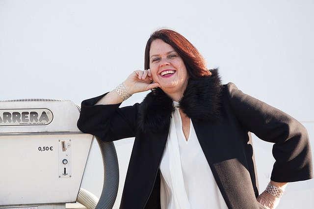 Eine Frau: weiße Bluse, schwarze Jacke, rote Haare, lehnt an einem Autostaubsauger und lacht.