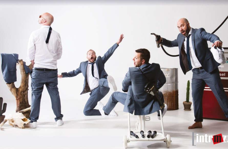 Vier Musiker in grauen Anzügen und weißen Hemden springen herum.