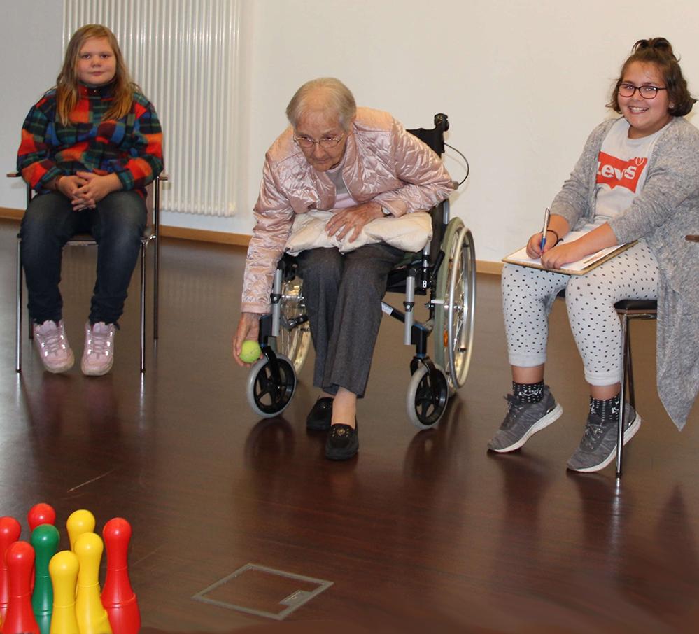 2 Mädchen kegel mit einer Seniorin die im Rollstuhl sitzt.