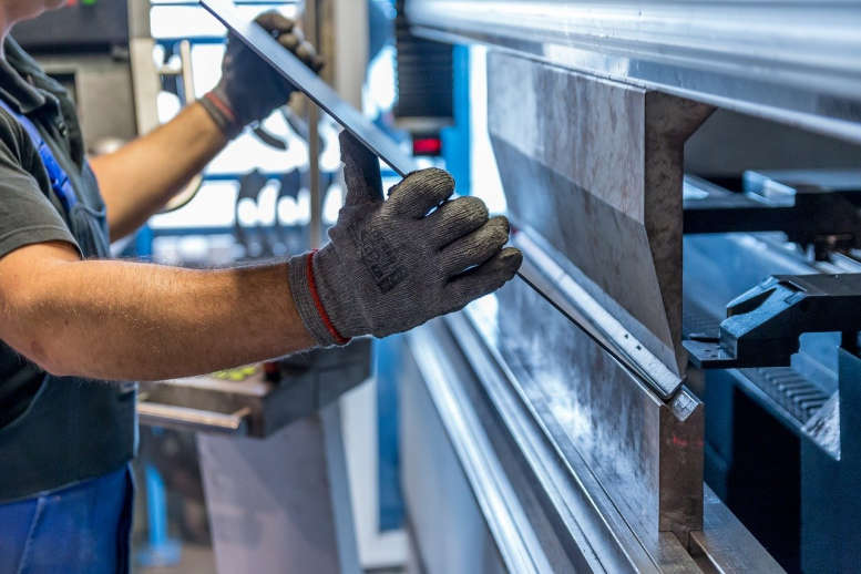 Hände in Arbeitshandschuhen die ein Blech in eine Kante/Walze legen.