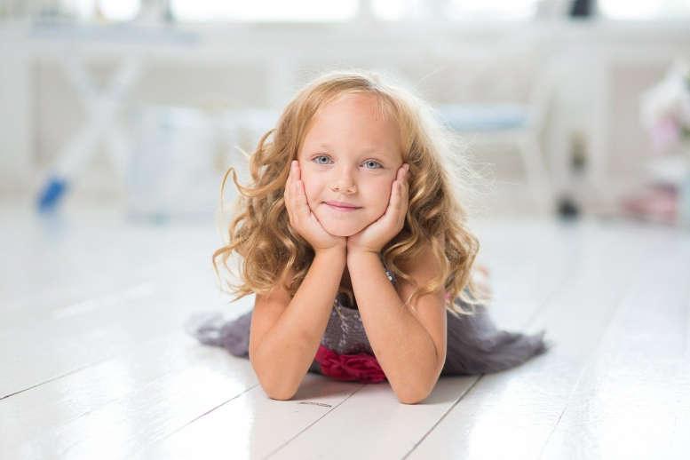 Ein Mädchen, etwa fünf Jahre schaut fröhlich in die Kamera.