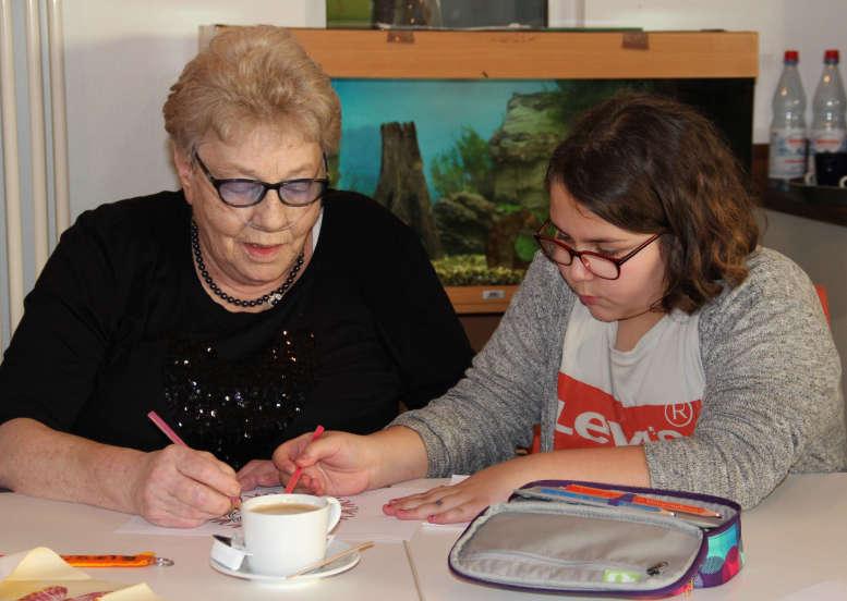 Seniorin und Schülerin sitzen am Tisch und malen.