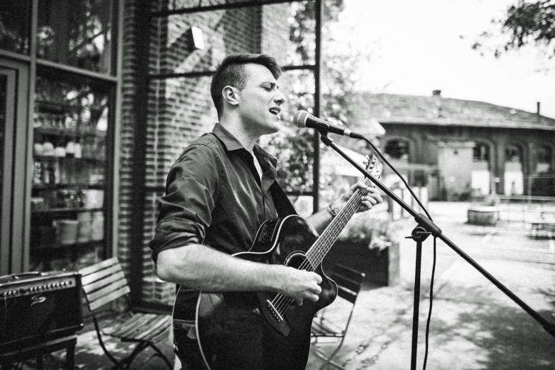 Junger Mann singt und spielt Gitarre vor einem Backsteinhaus.