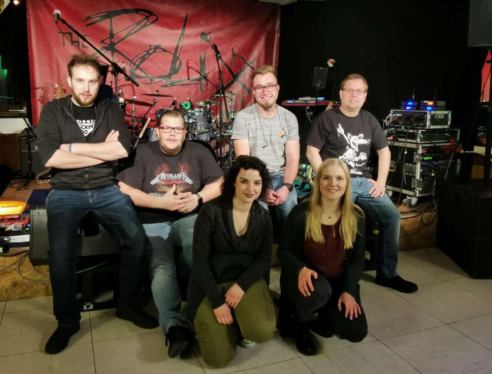4 Musiker, 2 Musikerinnen hocken zum Gruppenfoto vor ihrem Band-Logo. The Rolix.