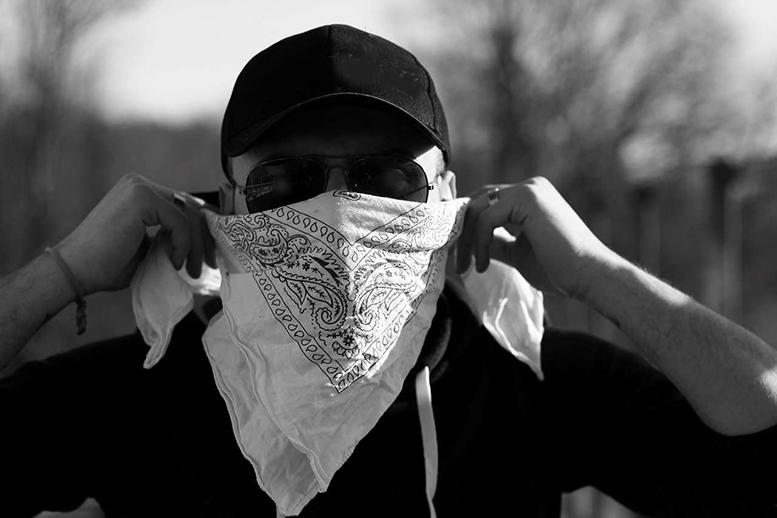 Vermummter Mann. Mütze, dunkel gekleidet, Tuch vor der unteren Gesichtshälfte.