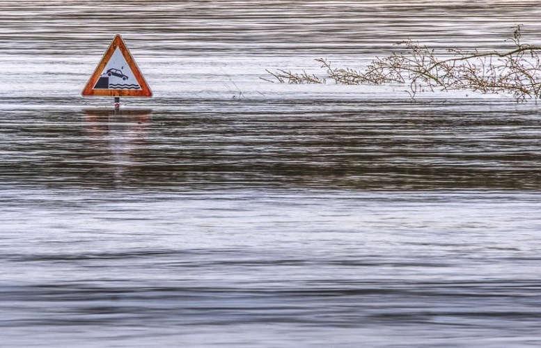 Eine überschwemmte Straße. Ein Schild: Achtung: Fluss.
