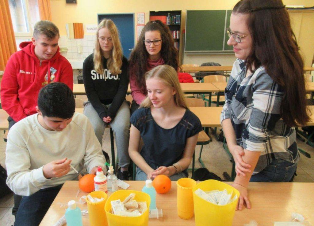 4 Schülerinnen und 2 Schüler sitzen um einen Tisch und ein Junge injiziert eine Flüssigkeit in eine Orange. Die anderen schauen zu.