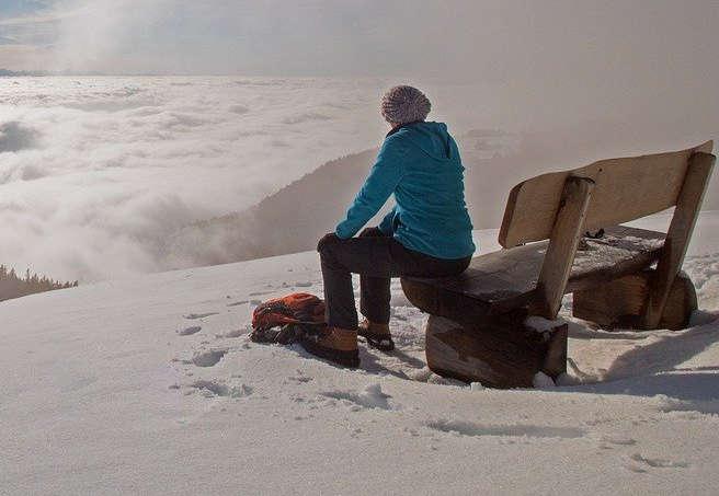 Frau sitzt in auf einer Bank im Schnee und bewundert die Aussicht.