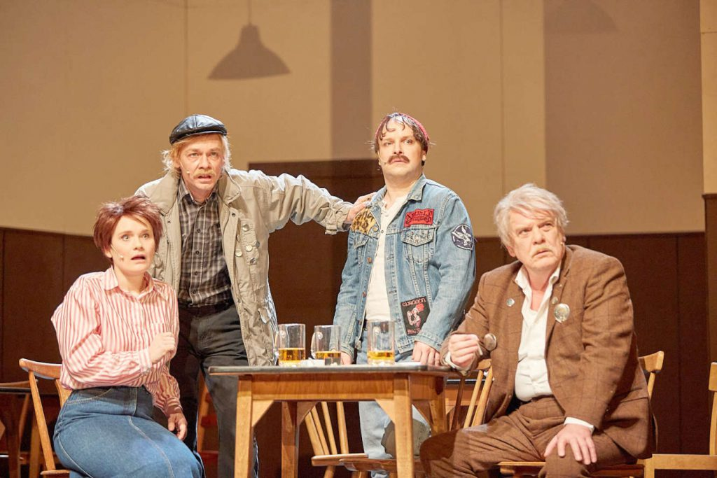 Vier Leute um einen Tisch herum: Schauspieler auf einer Theaterbühne.