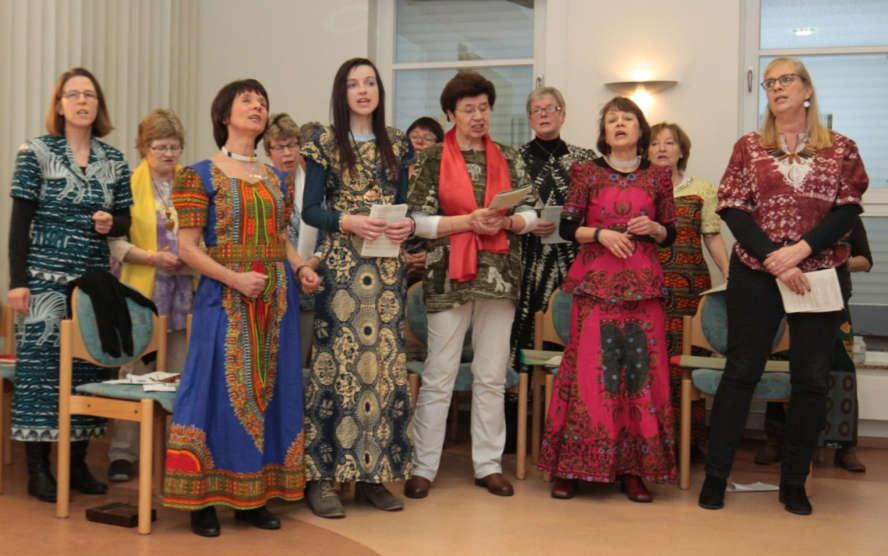 Frauen in afrikanischen Gewändern singen miteinander