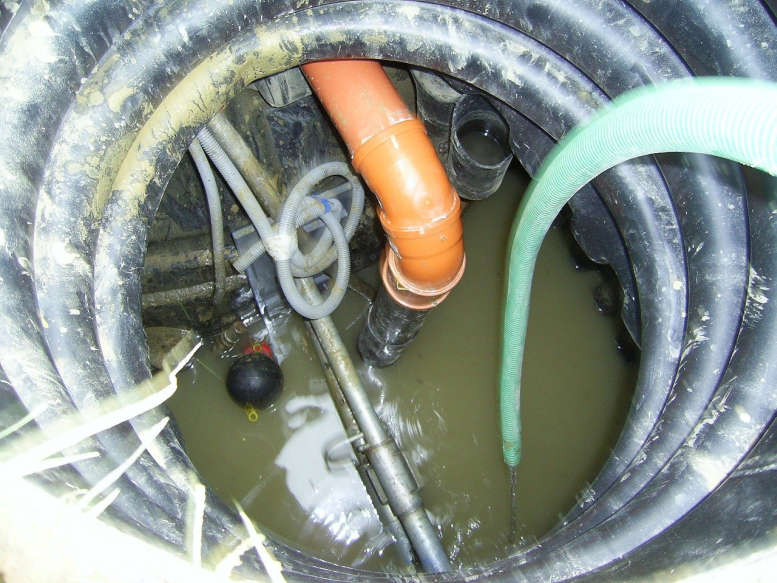 Kanal mit Schläuchen und Rohren und halb mit Wasser gefüllt