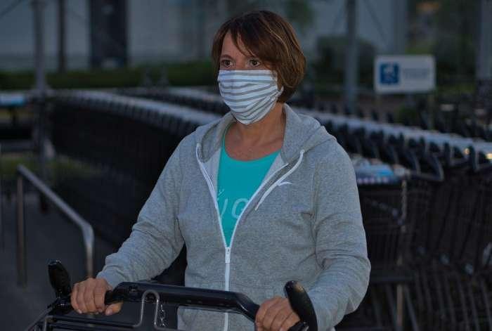 Frau mit Einkaufswagen und Mund-Nase-Maske kauft ein.