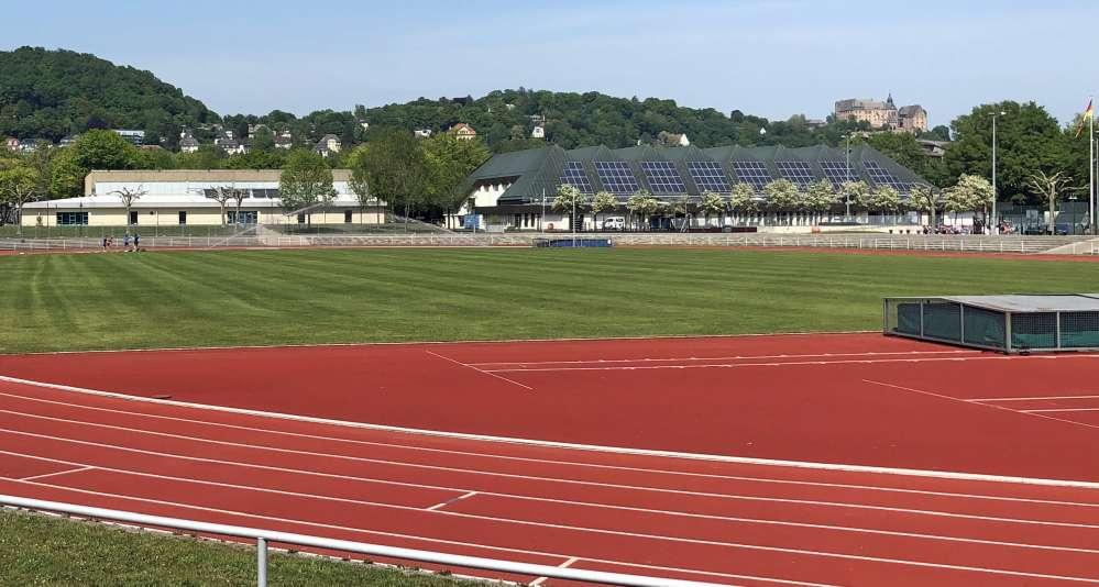Sportstadion. Dahinter Gebäude und oben am Berg das marburger Schloss