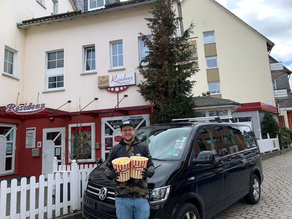 Mann mit 2 Eimern Popcorn vor einem Kino.