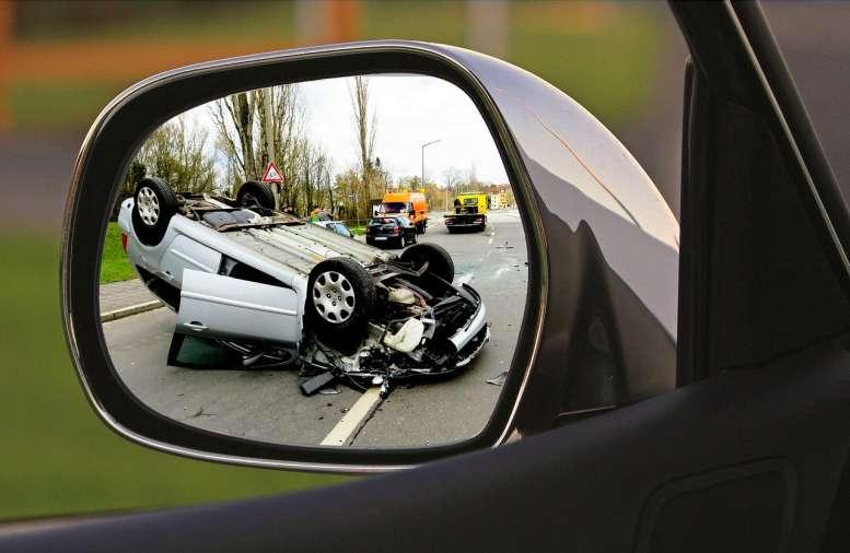 In einem Rückspielgel ist eine Unfallszenerie zu sehen - mit Abschleppwagen und Pkw