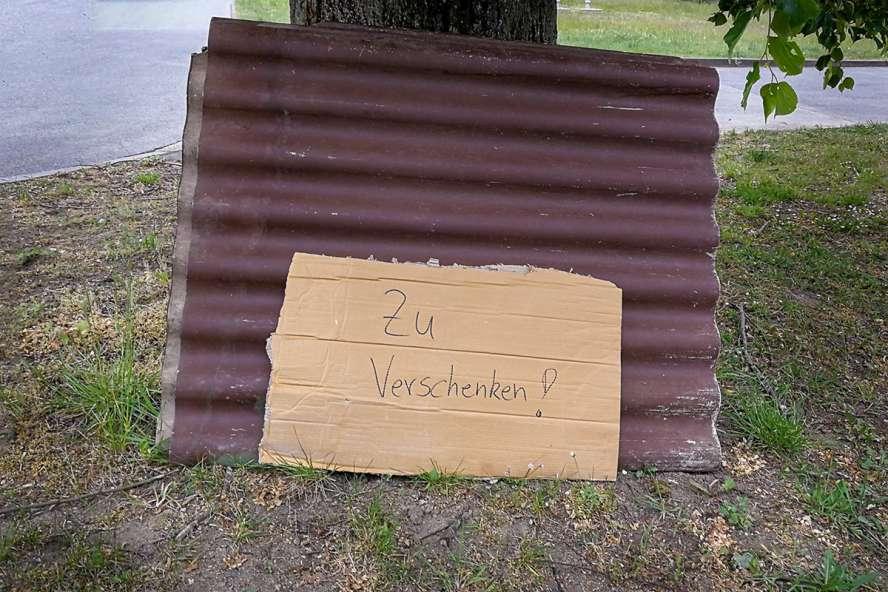 """Eternitplatten an Baum gelehnt. Schild dabei: """"zu verschenken""""."""