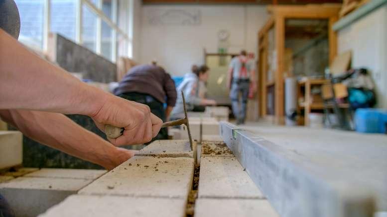 Handwerker mit Hammer, Säge und Kelle zugange