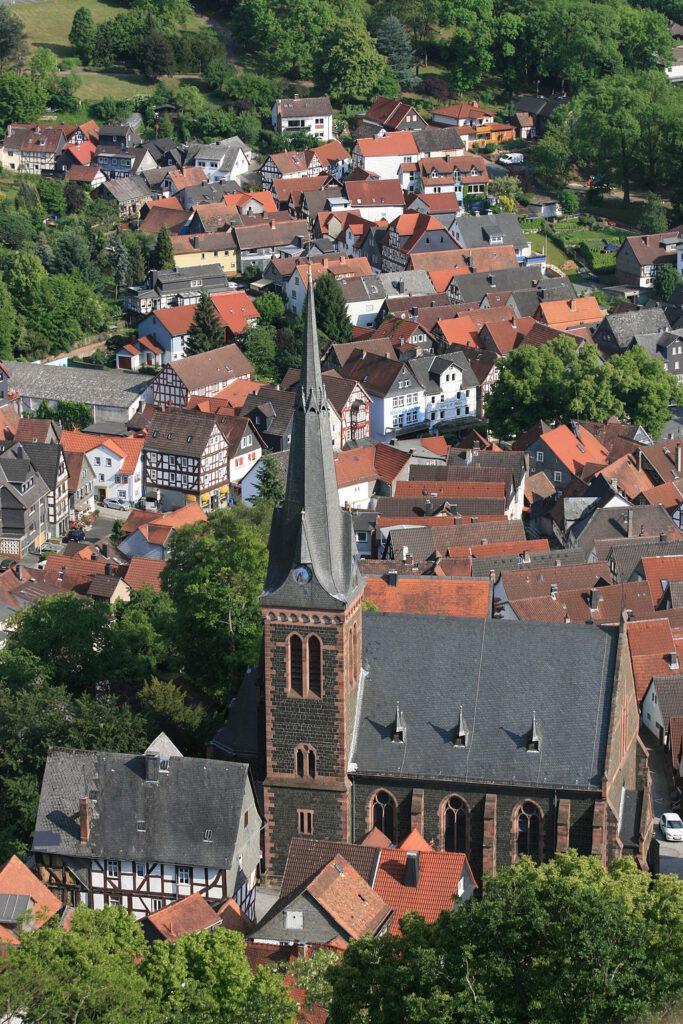 Altstadt mit Kirche und Kirchturm inmitten von Wald und Wiesen.