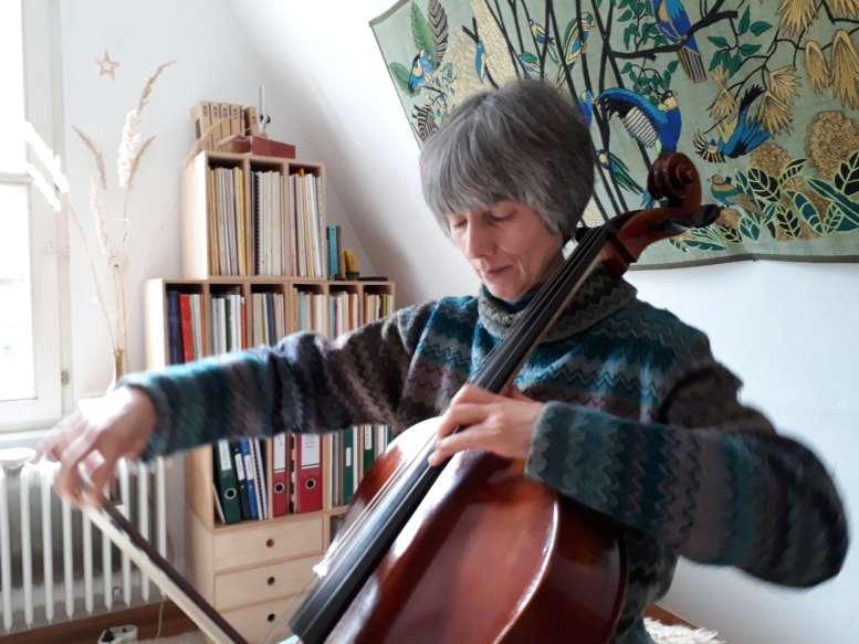Cellistin ins Spiel vertieft - vor einem Bücherregal