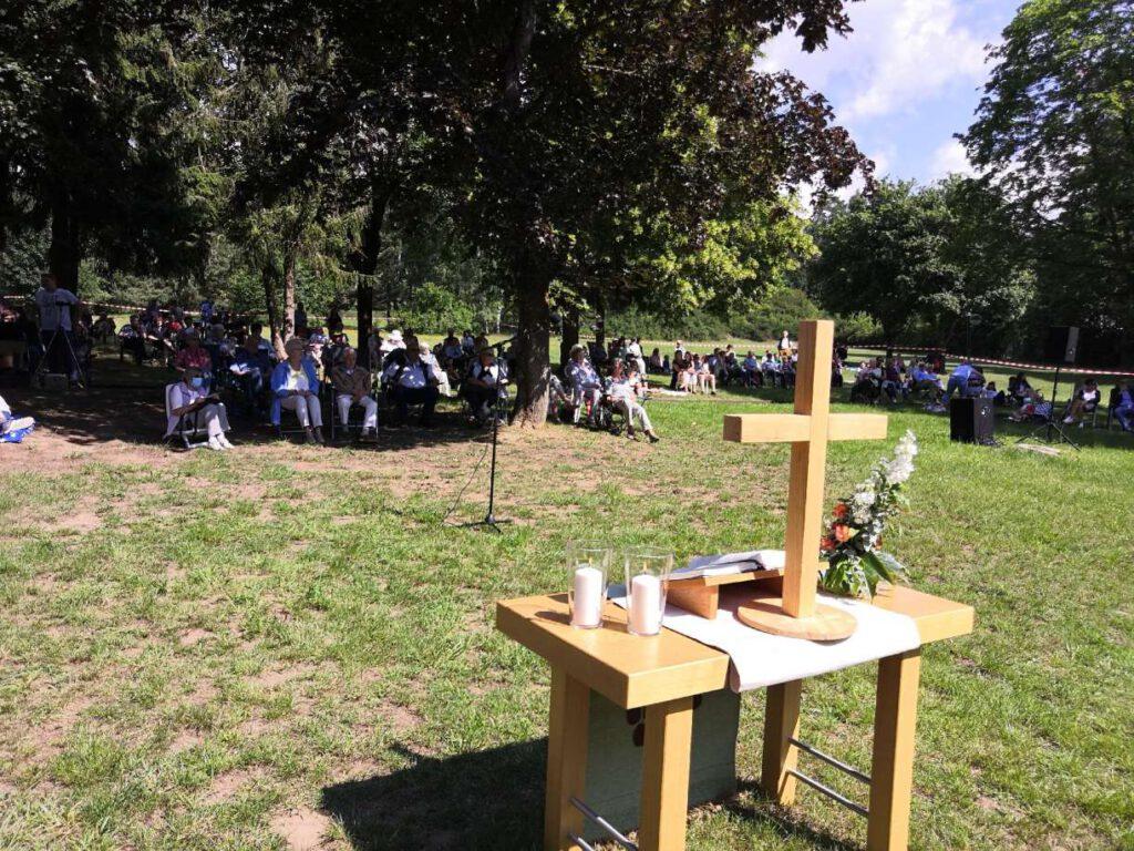 Altar mit Kreuz, Kerzen, Bibel auf einer Wiese. Dahinter auf Bänken und Klappstühlen die Gottesdienstbesucher