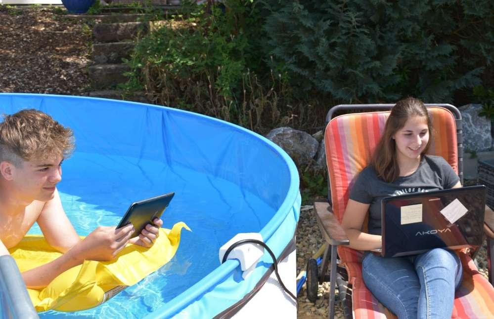 Junge auf Luftmatratze im Pool, Mädchen sitzt daneben. Beide am digitalen Endgerät