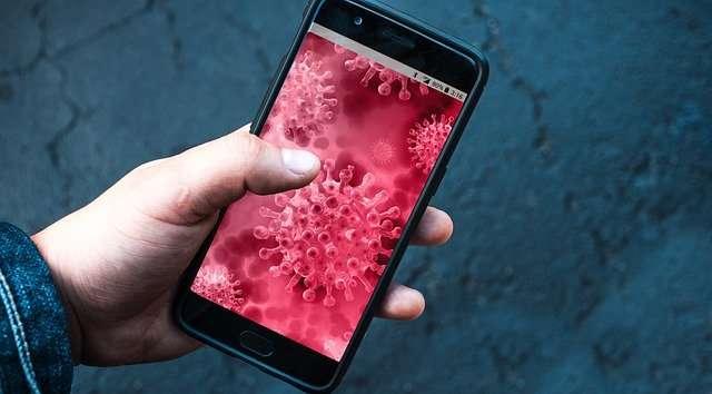 Eine Hand mit Smartphone. Es zeigt: Corona-Viren.