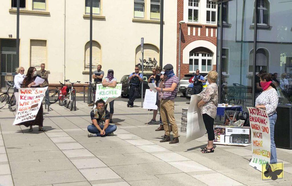 Leute mit Masken und Abstand demonstrieren mit Plakaten gegen die Coronamaßnahmen.