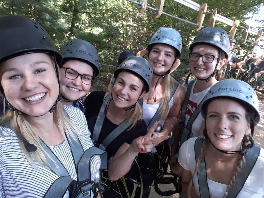 6 Jugendliche mit Helm im Kletterwald. Gruppenfoto.