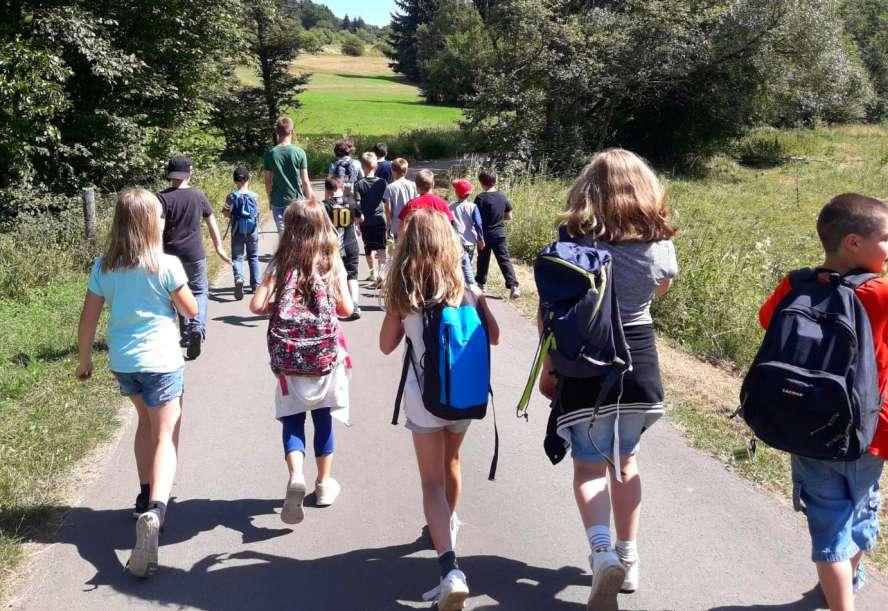 Kindergruppe wandert durch die Wiesen auf geteertem Weg. Alle von hinten zu sehen.