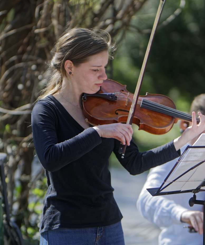 Frau spielt im Freien vor einem Baum Geige.