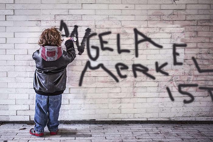 """Ein Kind sprüht Graffiti an eine Mauerwand. """"Angela Markel ist..."""""""