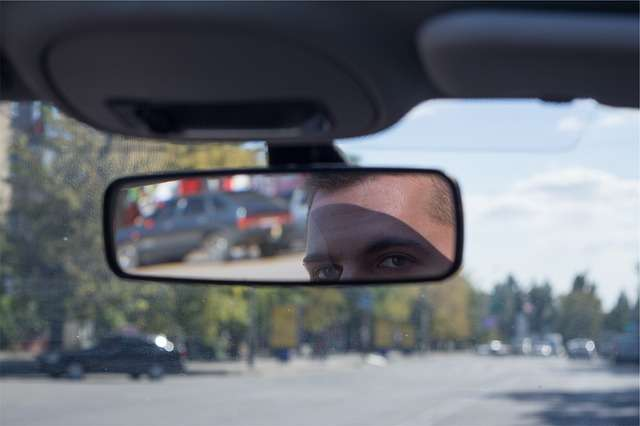 Innenraum im Auto. Mann schaut in den Rückspiegel