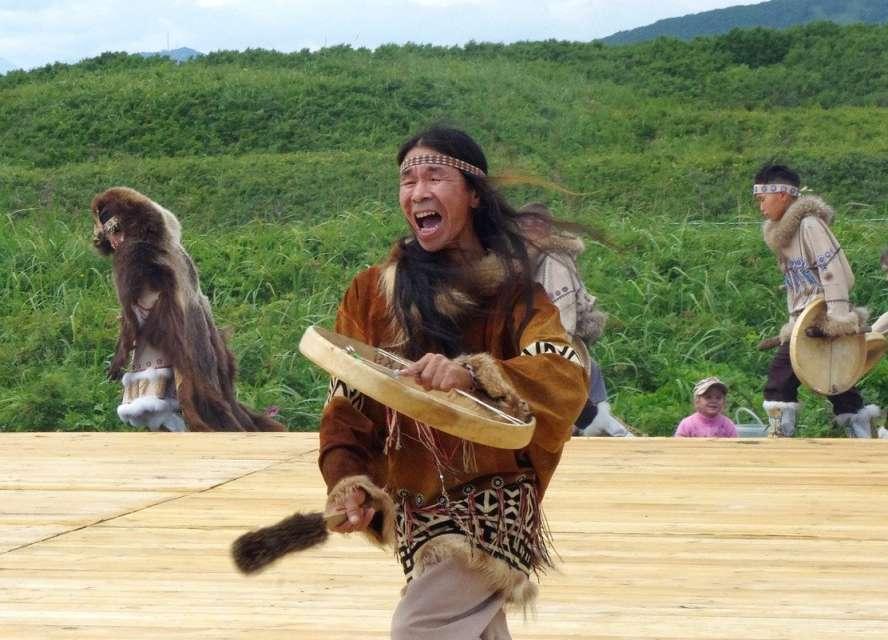 4 Indianer in Stammeskleidung springen und klopfen auf ihre Rahmentrommeln.