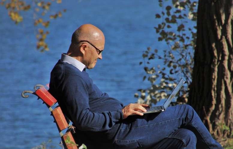Mann sitzt auf einer Bank am PC und arbeitet