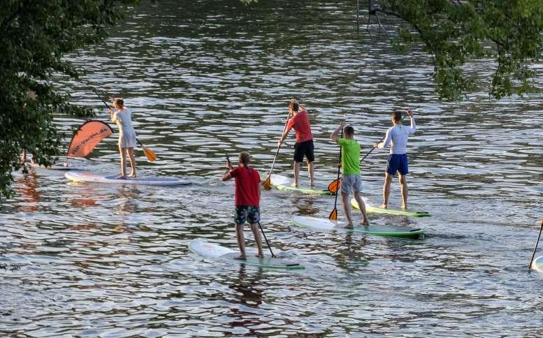 6 Jugendliche auf einem Fluss - beim Stand-Up-Paddling